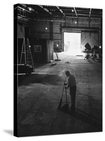 A Man Cleaning Up the Empty Sound Stage--Stretched Canvas Print