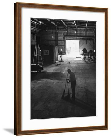 A Man Cleaning Up the Empty Sound Stage--Framed Photographic Print