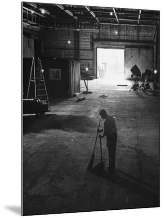 A Man Cleaning Up the Empty Sound Stage--Mounted Photographic Print