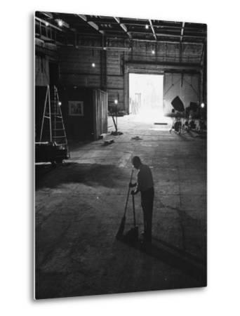 A Man Cleaning Up the Empty Sound Stage--Metal Print