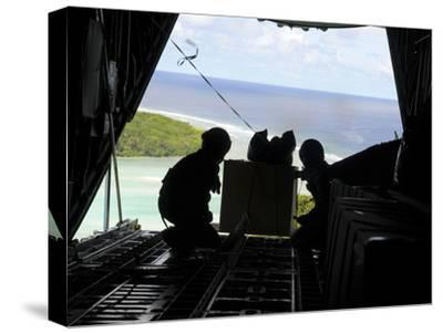 Airmen Push Out a Pallet of Donated Goods from a C-130 Hercules-Stocktrek Images-Stretched Canvas Print