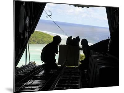 Airmen Push Out a Pallet of Donated Goods from a C-130 Hercules-Stocktrek Images-Mounted Photographic Print