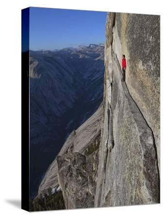 A climber walks a 40-foot-long sliver of granite on Half Dome, named the Thank God Ledge.-Jimmy Chin-Stretched Canvas Print