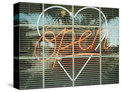 Neon 'Open' sign framed in a heart-shape in a window--Stretched Canvas Print
