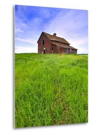 Abandoned red barn sitting on the top of a hill on a pioneer homestead in rural Alberta Canada-Robert McGouey-Metal Print