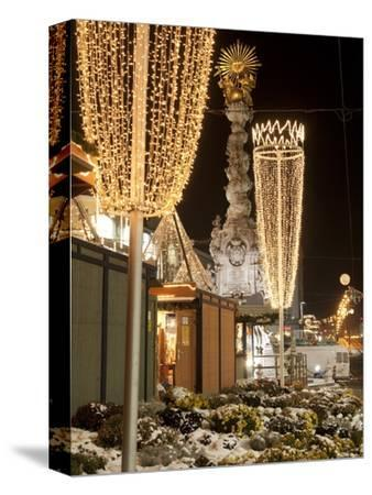 Snow-Covered Flowers, Christmas Decorations and Baroque Trinity Column at Christmas Market, Austria-Richard Nebesky-Stretched Canvas Print