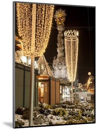 Snow-Covered Flowers, Christmas Decorations and Baroque Trinity Column at Christmas Market, Austria-Richard Nebesky-Mounted Photographic Print