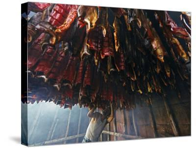 A Fisherman Checks the Salmon in His Smokehouse for Dryness-Michael Melford-Stretched Canvas Print