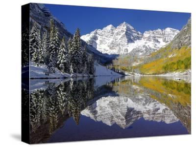 The Maroon Bells Casting Reflections in a Calm Lake in Autumn-Robbie George-Stretched Canvas Print