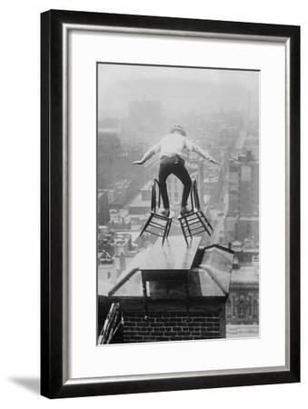 Reynolds Performs a Balancing Act on Roof in New York City--Framed Art Print