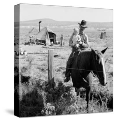 Cowboy Holds His Baby While Riding a Horse-Dorothea Lange-Stretched Canvas Print