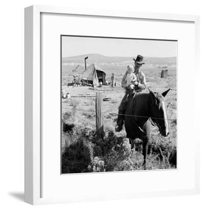 Cowboy Holds His Baby While Riding a Horse-Dorothea Lange-Framed Art Print