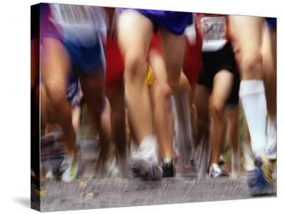 Blurred Action of Runner's Legs Competing in a Race--Stretched Canvas Print