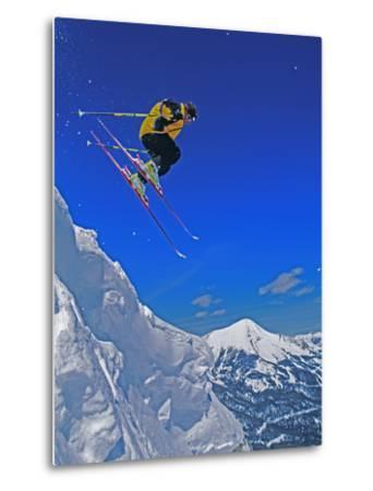 A Skier Jumps a Cornice at Exclusive Yellowstone Club Ski Area, Montana-Gordon Wiltsie-Metal Print