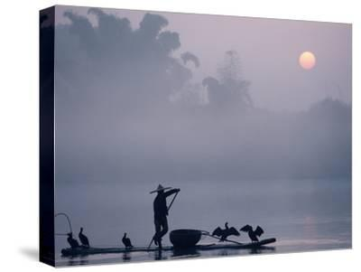 A Fisher Uses Cormorants to Capture Fish from the Li River at Sunrise-Kenneth Ginn-Stretched Canvas Print