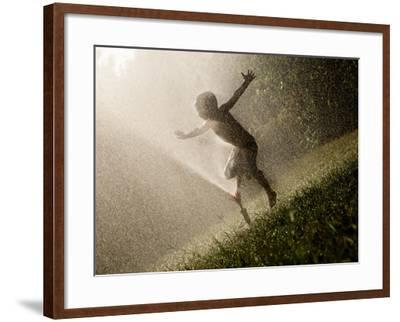 A Boy Plays in a Sprinkler on a Hot Summer Day-Heather Perry-Framed Photographic Print