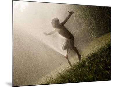 A Boy Plays in a Sprinkler on a Hot Summer Day-Heather Perry-Mounted Photographic Print