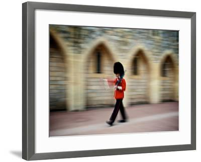 A Queen's Guard with a Rifle Walking Outside Windsor Castle-Heather Perry-Framed Photographic Print