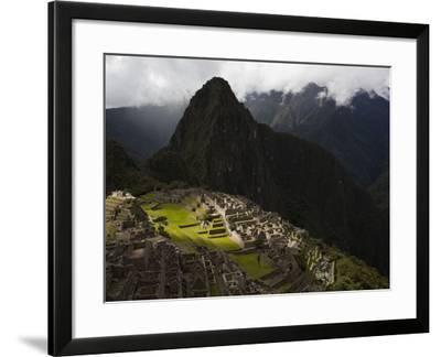 Sunlight Strikes Machu Picchu Through a Break in the Clouds-Michael Melford-Framed Photographic Print
