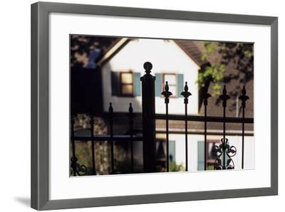 A Wrought Iron Black Fence Frames a Home with Blue Shuttered Windows-Paul Damien-Framed Photographic Print