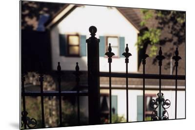 A Wrought Iron Black Fence Frames a Home with Blue Shuttered Windows-Paul Damien-Mounted Photographic Print