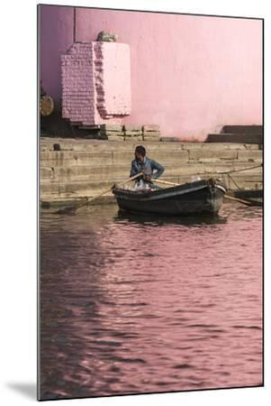 A Man in a Rowboat in Water Tinted Pink by Reflections of a Pink Wall-Jonathan Irish-Mounted Photographic Print