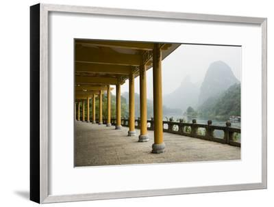 The Li River Runs Past a Covered Walkway by the Karst Formations-Jonathan Kingston-Framed Photographic Print