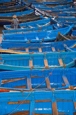 A Fisherman Stands in the Traditional Blue Boats of Essaouira Harbor-Cristina Mittermeier-Framed Photographic Print