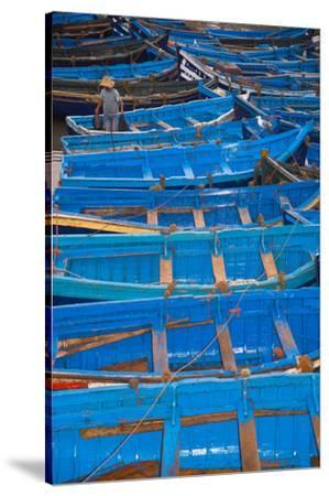 A Fisherman Stands in the Traditional Blue Boats of Essaouira Harbor-Cristina Mittermeier-Stretched Canvas Print