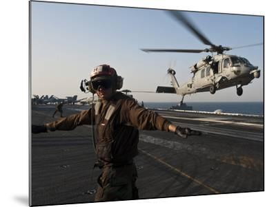 Airman Checks For a Clear Deck As An MH-60S Sea Hawk Takes Off USS John C. Stennis-Stocktrek Images-Mounted Photographic Print