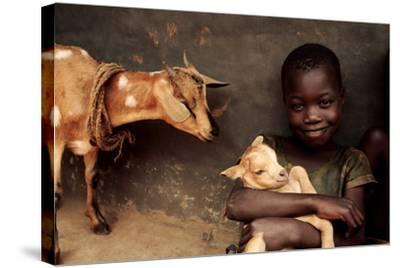 Child Holding a Kid-Mauro Fermariello-Stretched Canvas Print
