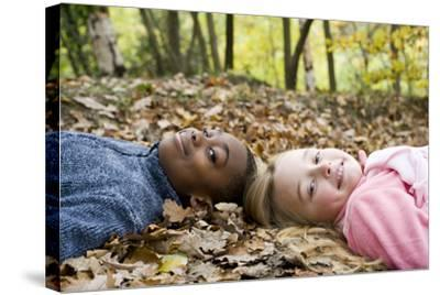 Smiling Children Lying on Autumn Leaves-Ian Boddy-Stretched Canvas Print