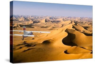 Small Plane Flying Above Giant Sand Dunes in Morning Light, Grand Erg Oriental, Algeria--Stretched Canvas Print