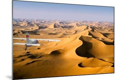 Small Plane Flying Above Giant Sand Dunes in Morning Light, Grand Erg Oriental, Algeria--Mounted Photographic Print