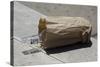 Discarded Rum Bottle In Paper Bag-Mark Williamson-Stretched Canvas Print