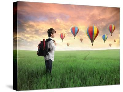 Child Carrying A Backpack Standing On A Green Meadow With Hot-Air Balloons In The Background-olly2-Stretched Canvas Print
