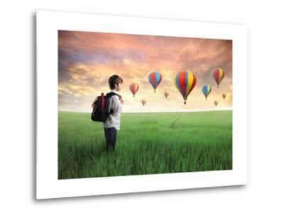 Child Carrying A Backpack Standing On A Green Meadow With Hot-Air Balloons In The Background-olly2-Metal Print