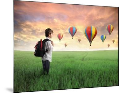 Child Carrying A Backpack Standing On A Green Meadow With Hot-Air Balloons In The Background-olly2-Mounted Art Print
