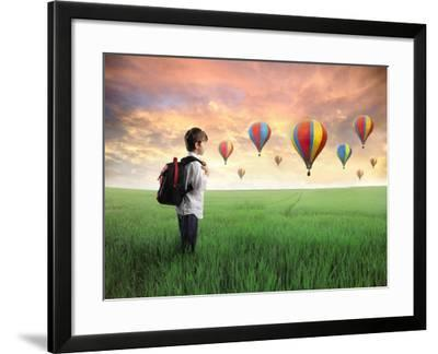 Child Carrying A Backpack Standing On A Green Meadow With Hot-Air Balloons In The Background-olly2-Framed Art Print