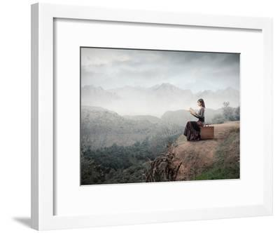 Woman Sitting On A Suitcase And Reading A Book With Landscape On The Background-olly2-Framed Art Print