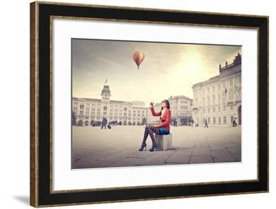Beautiful Woman In Colored Clothes On A Square With Hot-Air Balloon In The Background-olly2-Framed Art Print