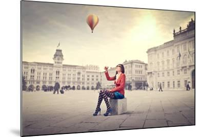 Beautiful Woman In Colored Clothes On A Square With Hot-Air Balloon In The Background-olly2-Mounted Art Print