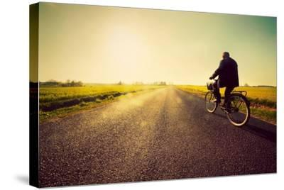Old Man Riding A Bike On Asphalt Road Towards The Sunny Sunset Sky-Michal Bednarek-Stretched Canvas Print