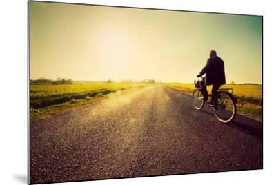 Old Man Riding A Bike On Asphalt Road Towards The Sunny Sunset Sky-Michal Bednarek-Mounted Art Print