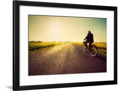 Old Man Riding A Bike On Asphalt Road Towards The Sunny Sunset Sky-Michal Bednarek-Framed Art Print