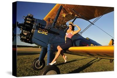 1940's Style Pin-Up Girl Sitting on the Wing of a Stearman Biplane--Stretched Canvas Print
