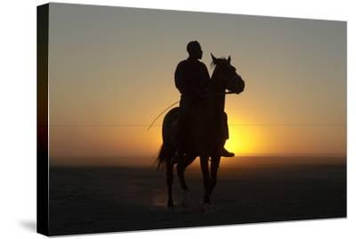 A Silhouetted Man on Horseback at Sunset-Beverly Joubert-Stretched Canvas Print