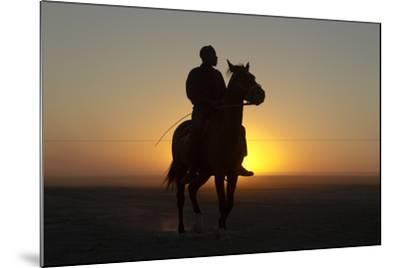 A Silhouetted Man on Horseback at Sunset-Beverly Joubert-Mounted Photographic Print