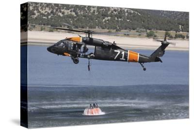 A U.S. Army Uh-60 Black Hawk Helicopter Collects Water from a Reservoir--Stretched Canvas Print