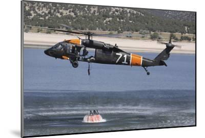 A U.S. Army Uh-60 Black Hawk Helicopter Collects Water from a Reservoir--Mounted Photographic Print